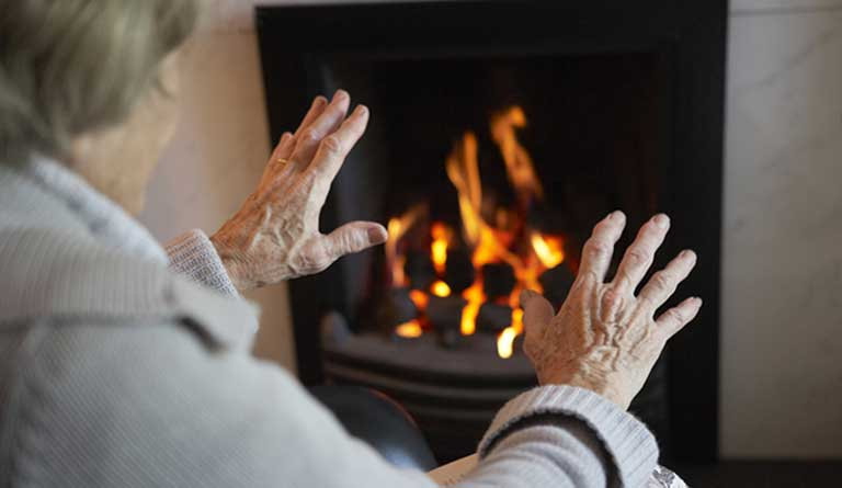lady warming hands at a fire